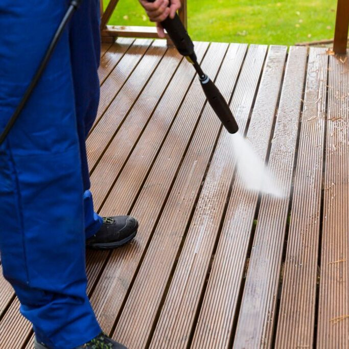man cleaning deck and patio